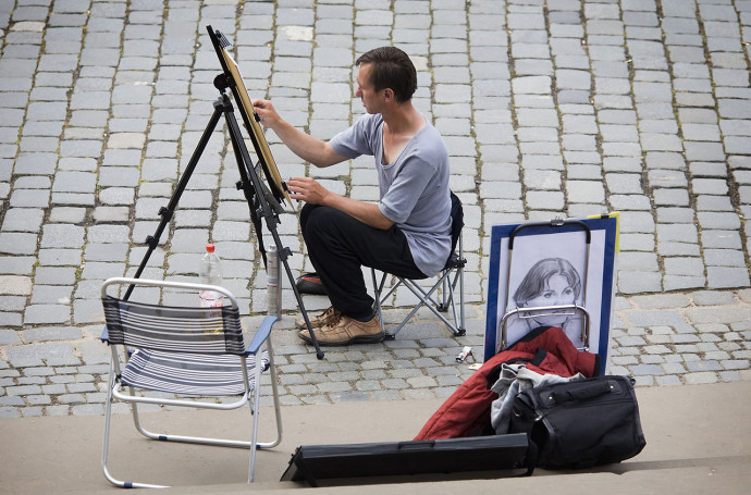 1280px-Street_artist_painting_in_a_painting_easel,_Dresden_-_1384